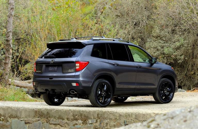 rear and side view of honda passport with black wheels