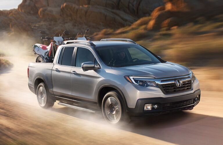 silver honda ridgeline driving in the desert carrying motorcycles
