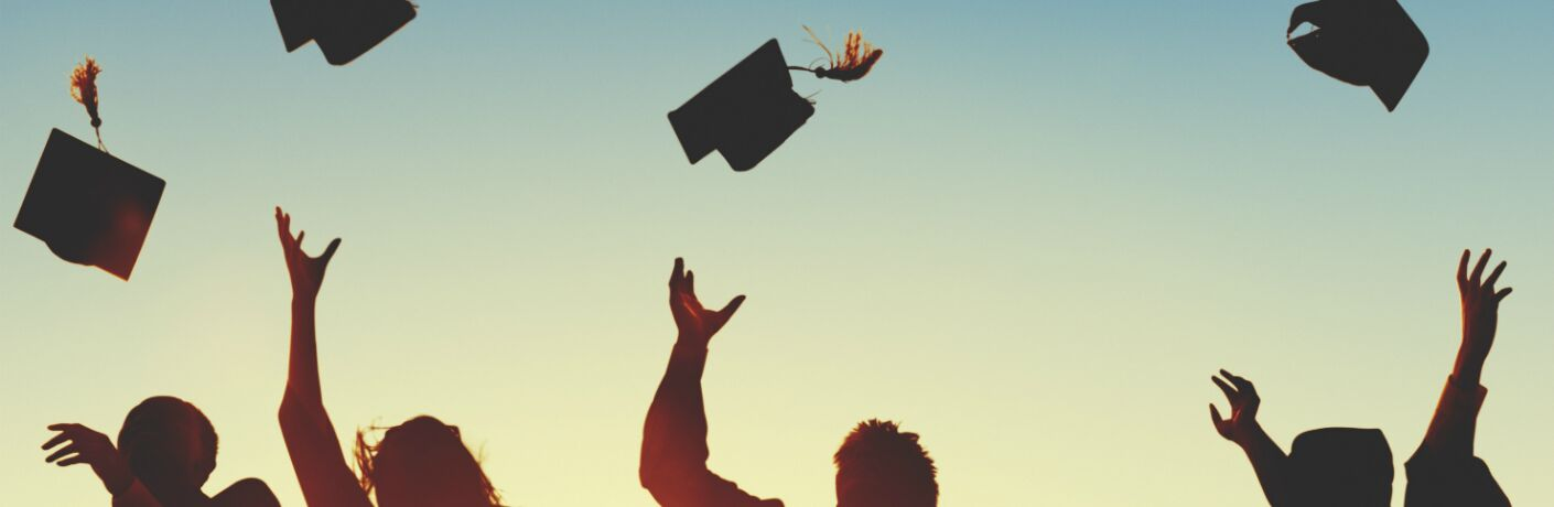 silhouette of graduates throwing caps in the air