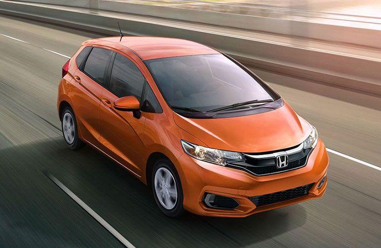 overhead view of orange Honda Fit on highway
