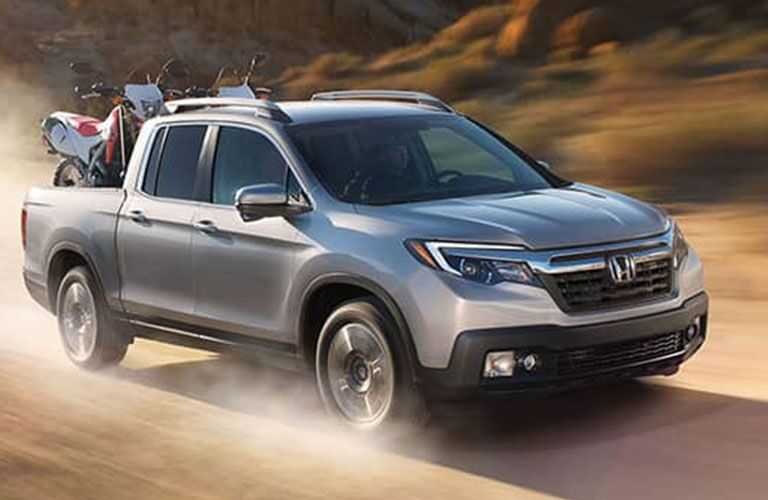 silver Honda Ridgeline carrying motorcycles driving on dirt mountain road