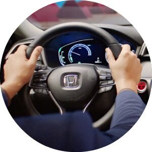 close-up view of hands on a Honda steering wheel
