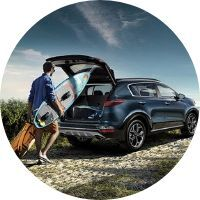 2020 Kia Sportage cargo area being loaded by man with surfboard