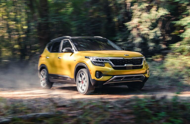 A front right quarter photo of the 2021 Kia Seltos driving through the woods.