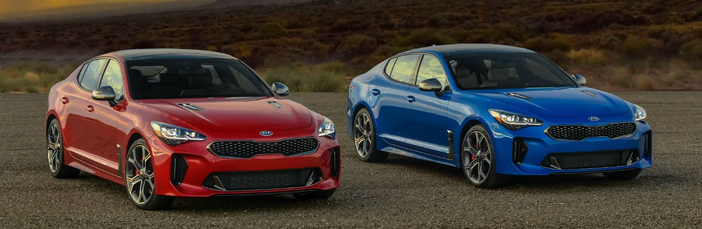 Two versions of the 2018 Kia Stinger sitting side-by-side.