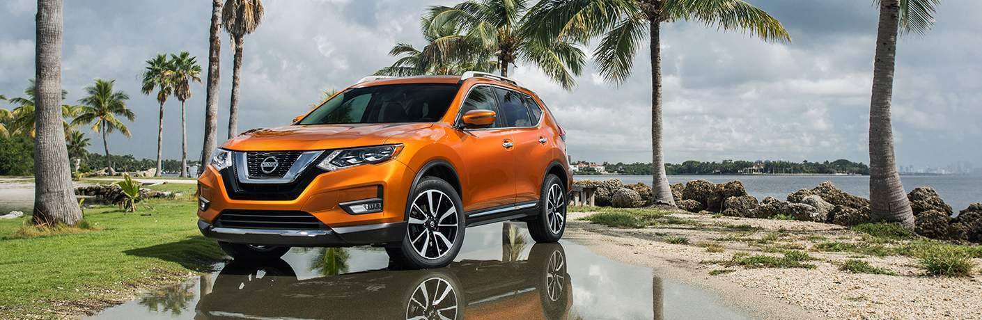Orange 2018 Nissan Rogue parked in front of palm trees and water