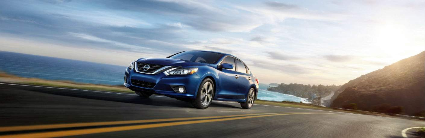 Blue 2018 Nissan Altima driving on curvy road next to ocean