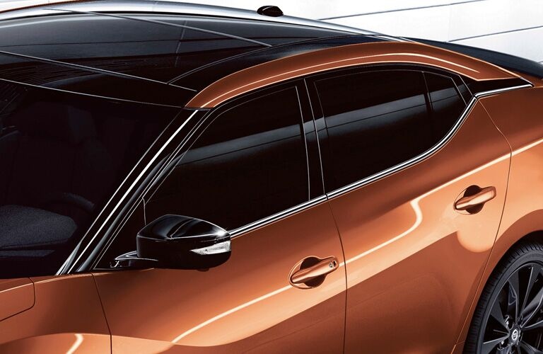 right side view of orange nissan maxima, tinted windows
