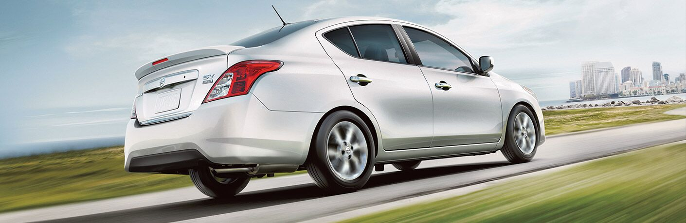 right side of white nissan versa driving