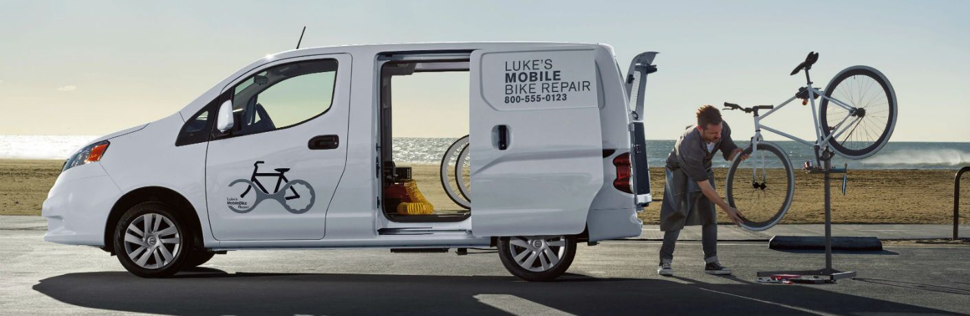 Driver side exterior view of a white 2019 Nissan NV200 Compact Cargo Van with a man repairing a bicycle behind it