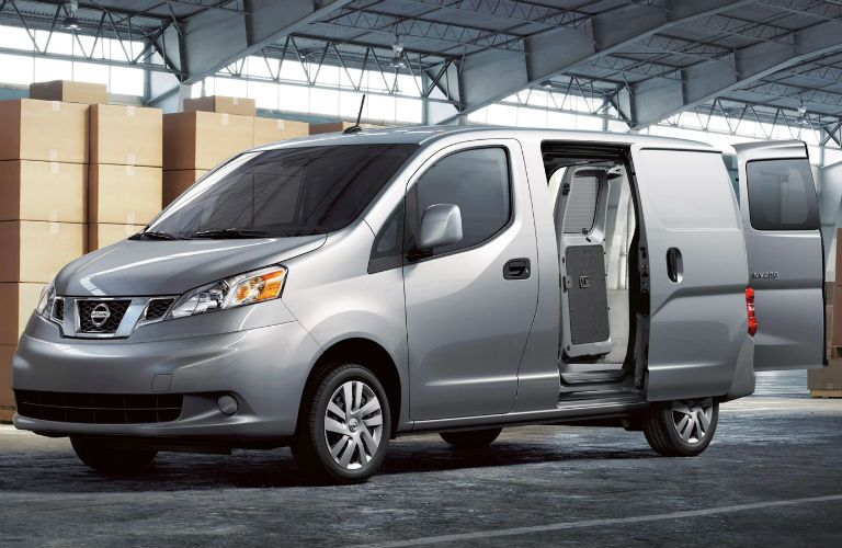 Front driver side exterior view of a gray 2019 Nissan NV200 Cargo Van with its side and rear doors open
