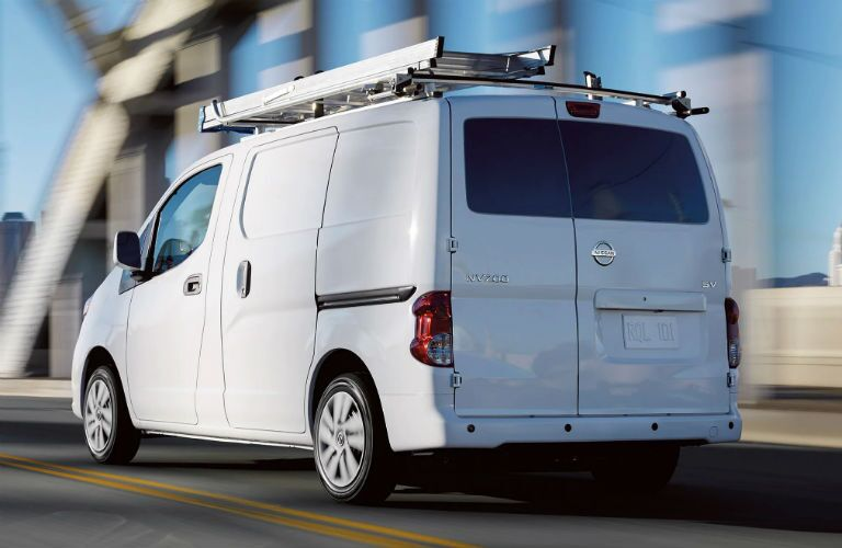 Rear driver side exterior view of a white 2019 Nissan NV200 Compact Cargo Van