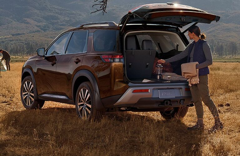 A woman getting cargo out of a 2022 Nissan Pathfinder