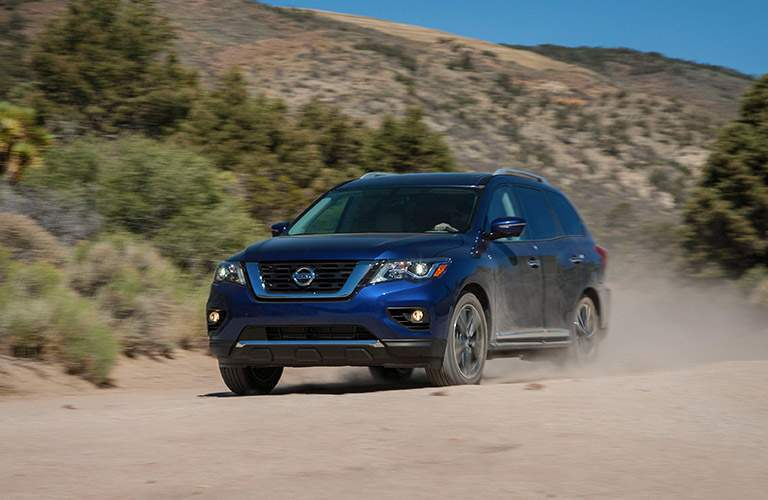 A front left quarter image of a blue 2018 Nissan Pathfinder driving over a desert trail