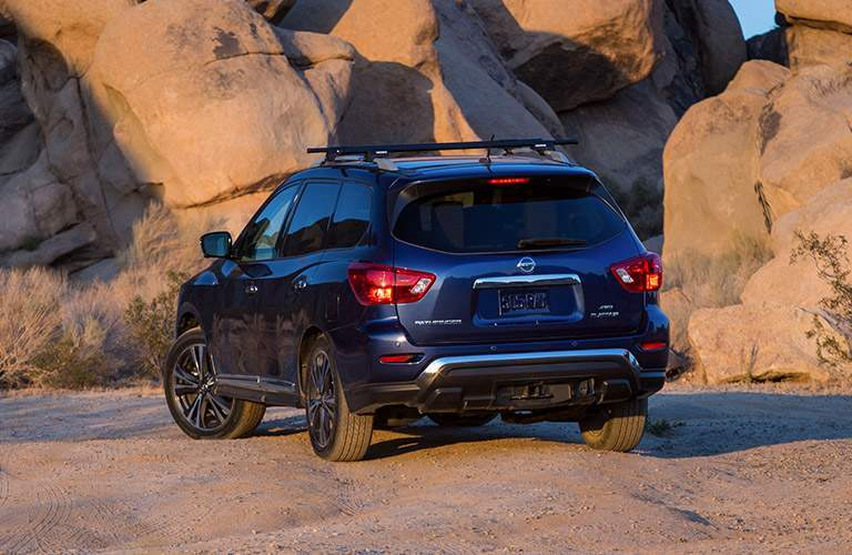 A rear view of a blue 2018 Nissan Pathfinder parked by desert rocks
