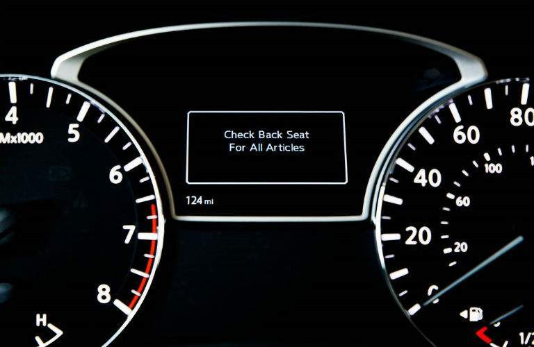 A close up photo of the rear seat reminder notification that is displayed in the center gauge cluster