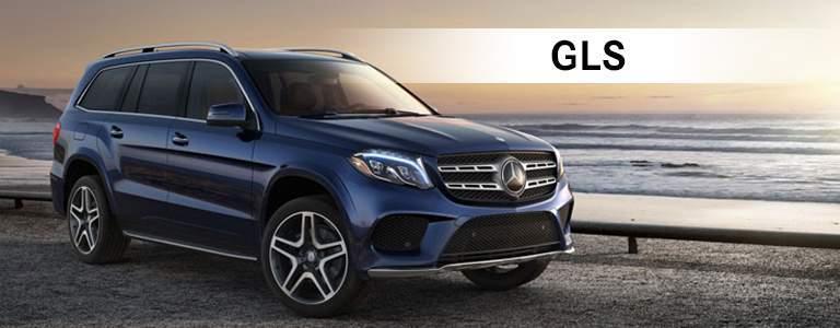 blue Mercedes-Benz GLS parked next to ocean with GLS text displayed