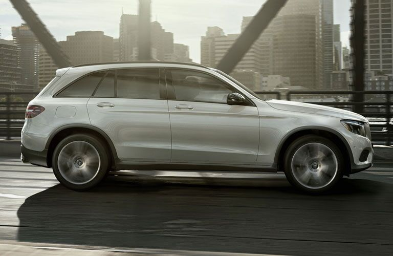 white 2018 Mercedes-Benz GLC driving across a bridge in a city with skyscrapers in the background