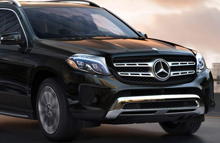 black Mercedes-Benz GLS SUV driving on the read with closeup view of grille