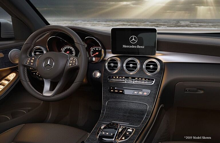 2020 Mercedes-Benz GLC interior shot from between front seats showing make logo on screen vents console and steering wheel