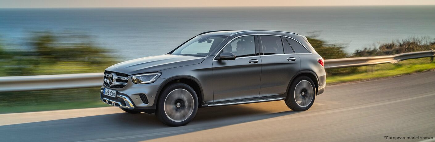2020 Mercedes-Benz GLC exterior shot grey driving on seaside road showing guardrail and motion blur