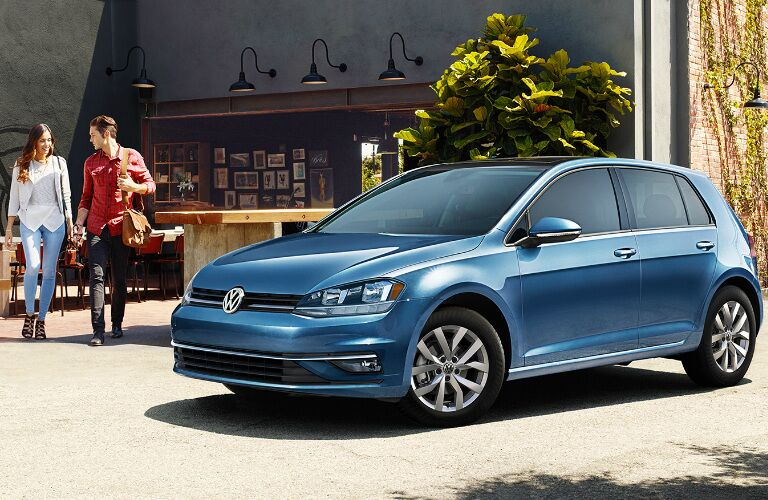 Woman and Man Walking by a Blue 2019 Volkswagen Golf