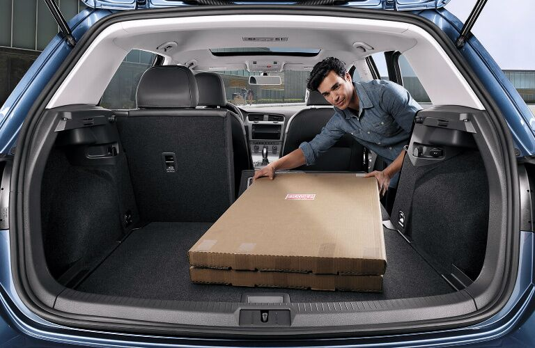 Man Loading a Box into the Cargo Area of a 2019 Volkswagen Golf