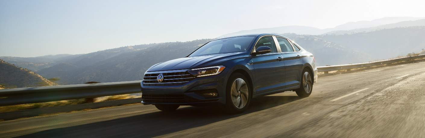 Blue 2019 Volkswagen Jetta Driving on a Mountainous Highway