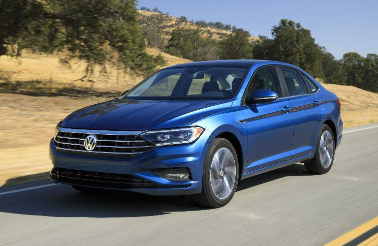 Blue 2019 Volkswagen Jetta Driving by Hilly Forested Area