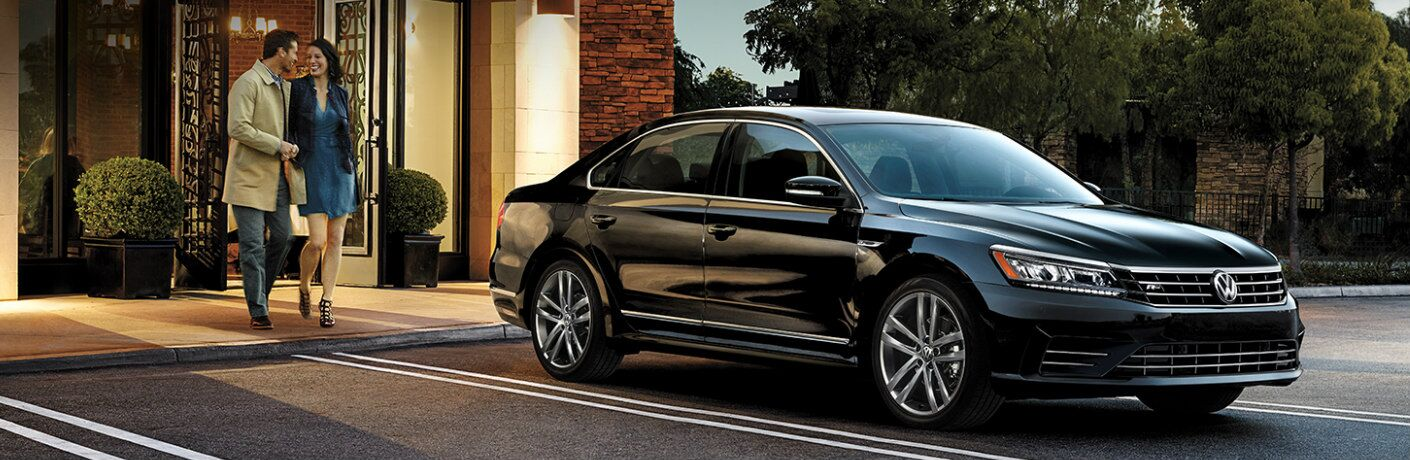 Man and Woman Walking by a Black 2019 Volkswagen Passat