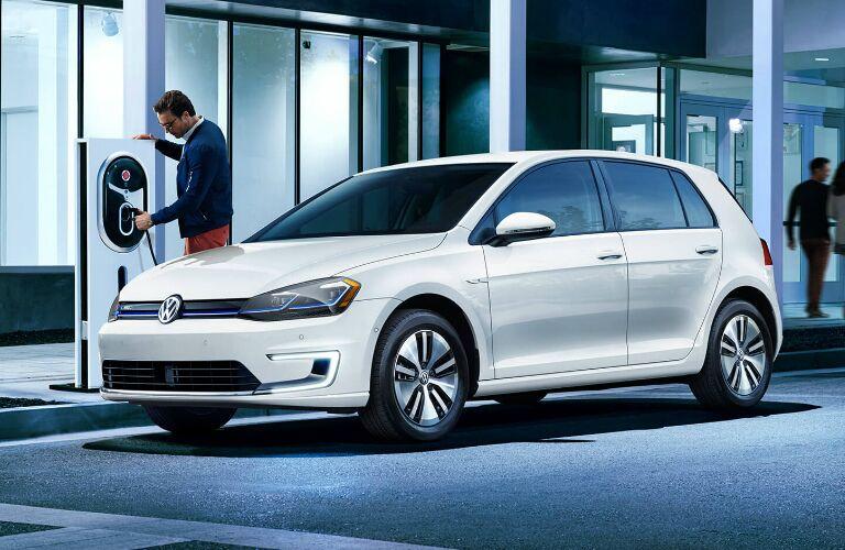 A man charging a white 2019 Volkswagen e-Golf
