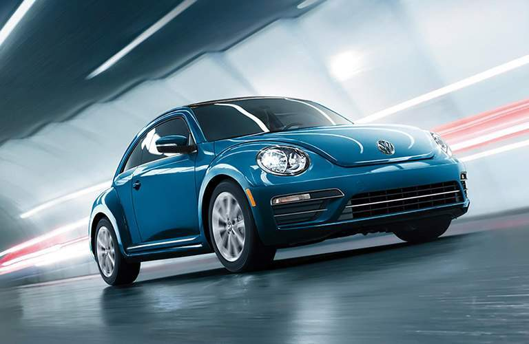 Blue Volkswagen Beetle driving through illuminated tunnel