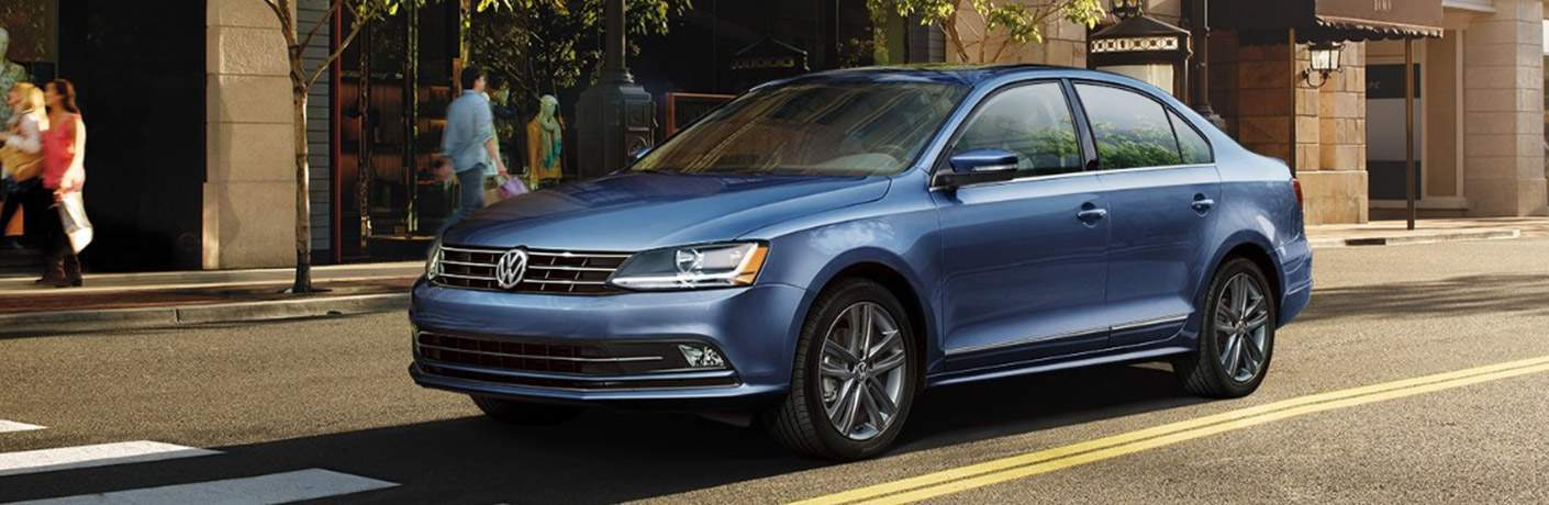 Blue 2018 Volkswagen Jetta stopped on city street with pedestrians walking on sidewalk