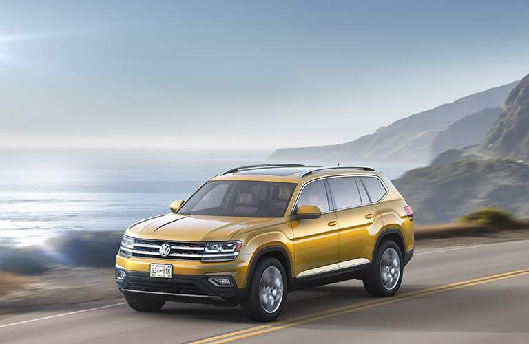 Yellow Volkswagen Atlas driving down waterfront road