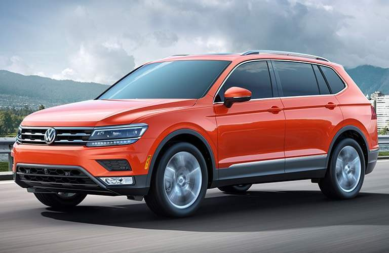 Orange Volkswagen Tiguan model driving down road with mountains in background