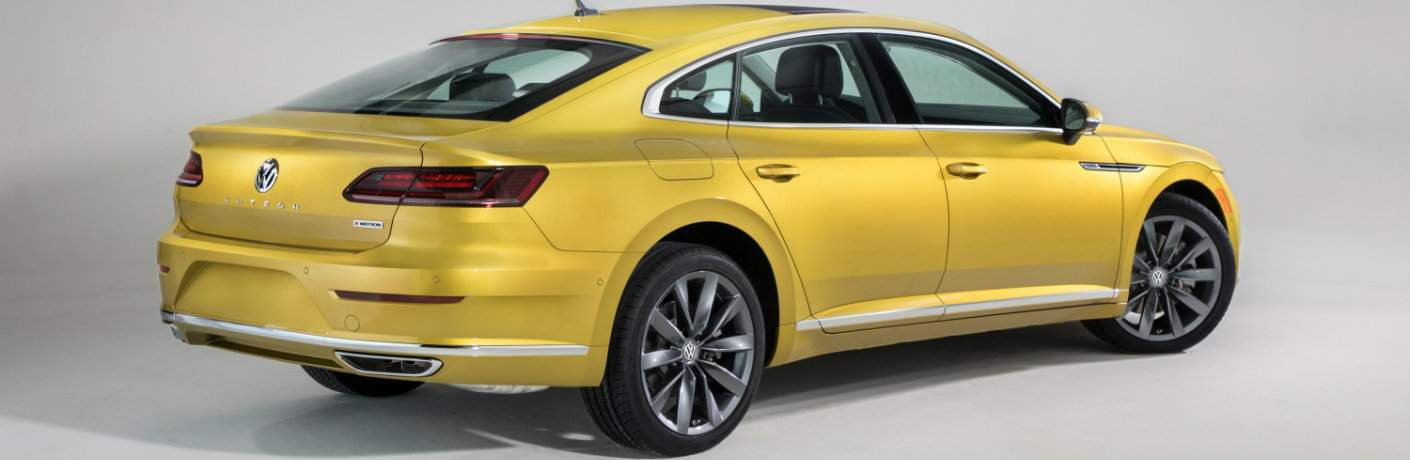 Rear shot of yellow 2019 Volkswagen Arteon on silver background