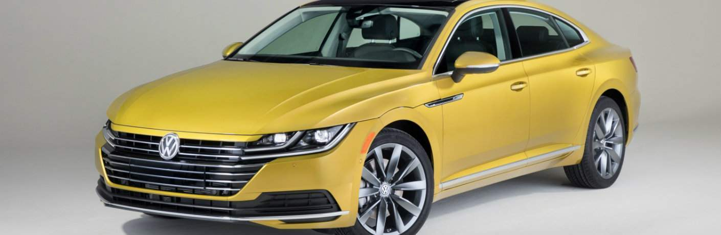 Front shot of yellow 2019 Volkswagen Arteon on silver background