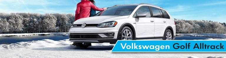 Two people sitting on Volkswagen Golf Alltrack model with frozen lake and snow covered trees in distance