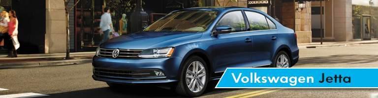 Blue Volkswagen Jetta model driving down busy city street in daytime