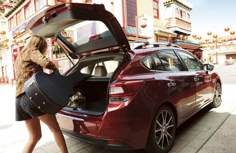 Woman loading a guitar in the 2018 Subaru Impreza