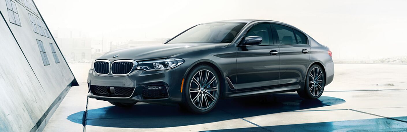2018 BMW 5-Series by a modern building