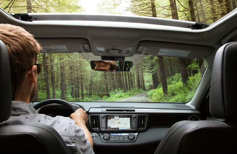 Man driving a 2018 Toyota RAV4 in the woods
