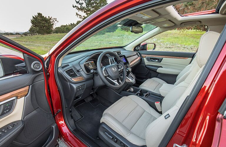 Open door of the 2019 Honda CR-V revealing the front seats and dashboard