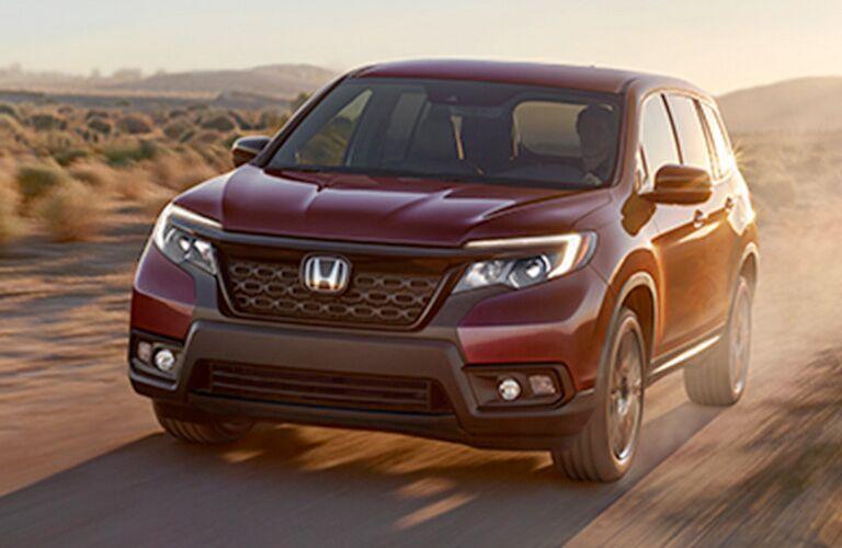 2019 Honda Passport exterior shot with red paint color driving through a desert near sand dunes