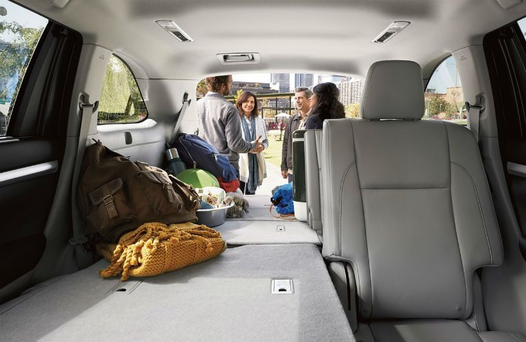 People talking outside the open hatch of the 2019 Toyota Highlander