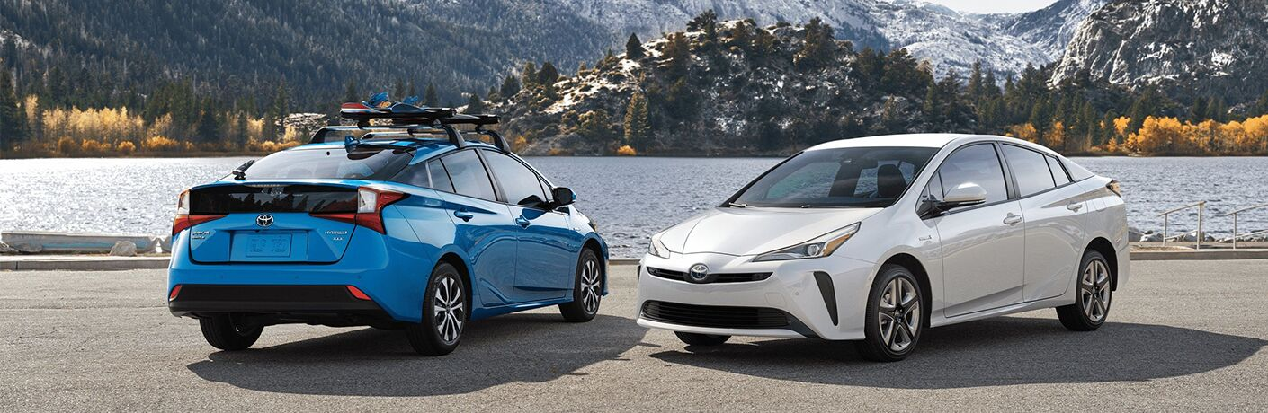 Two, 2020 Toyota Prius models parked side-by-side next to a lake with mountains in the background