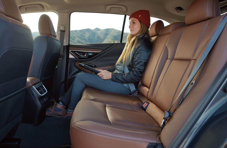 A woman sitting in the backseat of a 2020 Subaru Outback