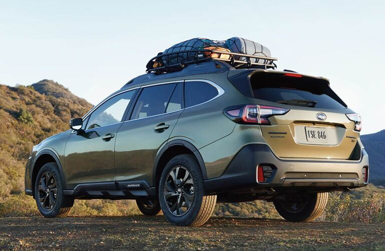 2021 Subaru Outback parked on a mountain with a roof basket full of supplies and gear