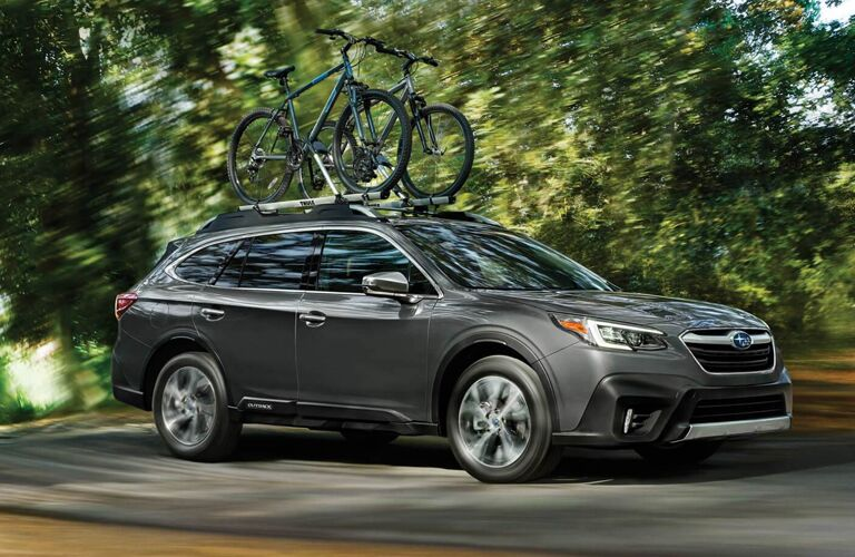 A 2020 Subaru Outback with bikes mounted on its roof driving down a road in the forest