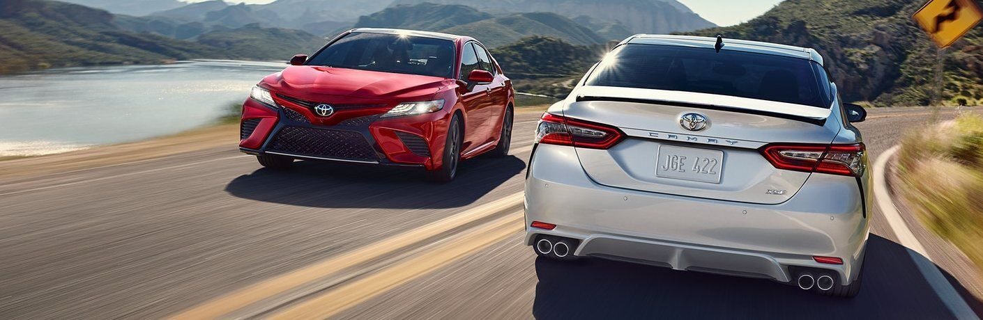 Two 2020 Toyota Camry models passing one another on a curving road
